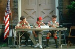 Três escuteiros do menino assentados na tabela Fotografia de Stock Royalty Free