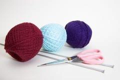 Três esferas de lãs, agulhas de confecção de malhas e tesouras Fotografia de Stock Royalty Free