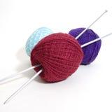 Três esferas de lãs e agulhas de confecção de malhas Foto de Stock Royalty Free