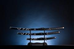 Três espadas no fundo azul. Copie o espaço. imagem de stock