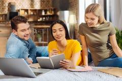 Três estudantes bonitos agradáveis que discutem trabalhos de casa fotos de stock