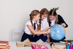 Três estudantes das meninas na lição da geografia com um globo na escola imagem de stock royalty free