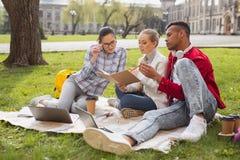 Três estudantes do mestrado que participam no projeto do negócio imagem de stock royalty free