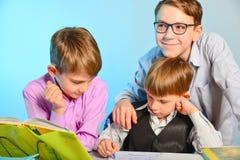 Três estudantes fazem lições da escola junto, resolvem tarefas dos trabalhos de casa fotografia de stock royalty free