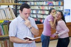 Três estudantes na biblioteca fotografia de stock royalty free