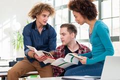 Três estudantes que comparam a informação de dois livros de texto diferentes Fotos de Stock Royalty Free