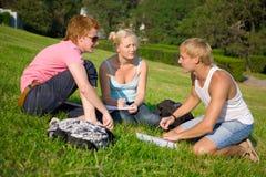 Três estudantes que falam no parque Imagens de Stock