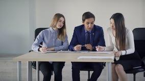 Três estudantes que falam o assento na tabela na sala de aula vídeos de arquivo