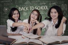 Três estudantes que juntam-se às mãos Fotos de Stock Royalty Free