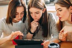 Três estudantes que leem o artigo usando o PC da tabuleta na ruptura de café fotos de stock