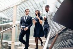 Três executivos multirraciais que andam para baixo em escadas com tabuleta digital imagem de stock