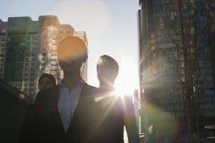 Três executivos que andam abaixo de uma rua da cidade com luz solar em sua parte traseira, alargamento da lente fotografia de stock royalty free