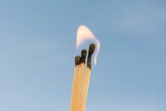 Três fósforos ardentes em um fundo azul Imagens de Stock