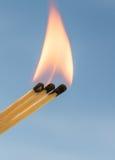 Três fósforos ardentes em um fundo azul Fotografia de Stock