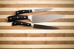 Três facas de cozinha sobre a placa de corte de bambu Imagens de Stock