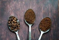 Três fases das colheres no café - feijões, terra, imediata Foto de Stock Royalty Free
