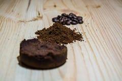 Três fases para a preparação do café: grão, esmagamento e a tabuleta pressionada Superfície de madeira espresso Barista do trabal foto de stock