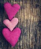 Três fazem crochê corações cor-de-rosa no fundo de madeira Foto de Stock