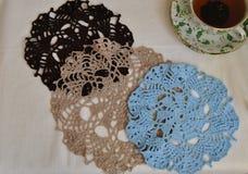 Três fazem crochê o doily de cores diferentes e o copo do chá Fotografia de Stock Royalty Free