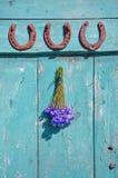 Três ferraduras e grupos das centáureas que penduram sobre oldwooden a porta imagem de stock royalty free