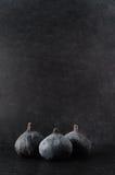 Três figos agrupados no preto Fotos de Stock Royalty Free
