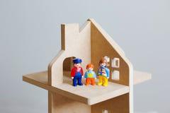 Três figuras do brinquedo do homem dos homens-um, de uma mulher e de uma criança em uma casa de madeira do brinquedo Um símbolo d imagens de stock