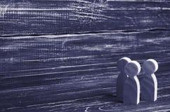 Três figuras humanas de madeira estão junto Conceito social imagens de stock royalty free