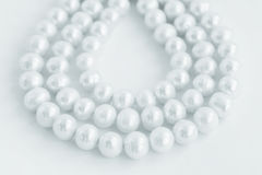 Três fileiras da colar da pérola natural no branco Fotografia de Stock Royalty Free