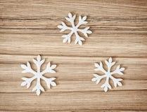 Três flocos de neve brancos no fundo de madeira, decorati do inverno Fotos de Stock Royalty Free