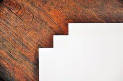 Três folhas do Livro Branco que encontram-se em uma superfície de madeira Imagens de Stock