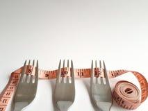Três forquilhas com uma fita mesuring rolaram neles Imagem de Stock