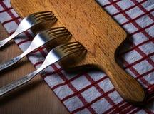 Três forquilhas em uma placa de madeira da cozinha Fotografia de Stock