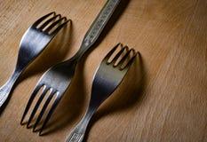 Três forquilhas em uma placa de madeira na máscara Imagens de Stock Royalty Free