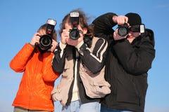 Três fotógrafo de encontro ao céu azul imagens de stock