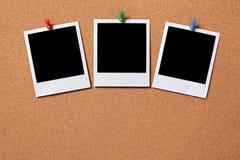 Três fotos vazias fixadas a uma placa da cortiça Fotos de Stock Royalty Free