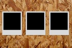 Três frames vazios da foto no fundo de madeira Imagens de Stock