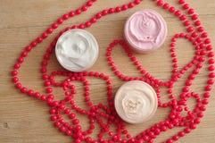 Três frascos da loção do corpo indicados com cordas de grânulos cor-de-rosa Fotos de Stock Royalty Free