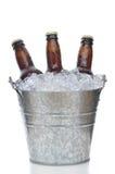 Três frascos de cerveja de Brown na cubeta de gelo Foto de Stock