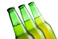 Três frascos de cerveja verdes isolados Foto de Stock