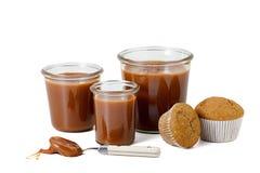 Três frascos de queques e da colher salgados do caramelo Fotos de Stock