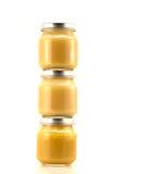 Três frascos de vidro do suporte do puré do fruto do bebê Imagens de Stock Royalty Free