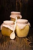Três frascos do mel em um fundo de madeira Imagem de Stock