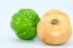Três frescos e produtos saudáveis em um fundo branco: pimenta verde e dois bulbos foto de stock