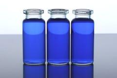 Três garrafas com líquido azul foto de stock