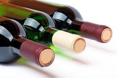 Três garrafas com vinho vermelho e branco Fotografia de Stock