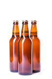 Três garrafas da cerveja gelado isoladas no branco Imagem de Stock