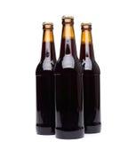 Três garrafas da cerveja no fundo branco. Imagem de Stock