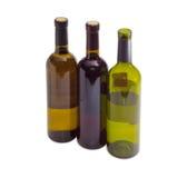 Três garrafas de um vário vinho em um fundo claro fotografia de stock royalty free