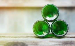 Três garrafas de vidro, partes inferiores verdes encontram-se adiante em de madeira Fotos de Stock Royalty Free