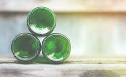 Três garrafas de vidro, partes inferiores verdes encontram-se adiante em de madeira Fotografia de Stock Royalty Free